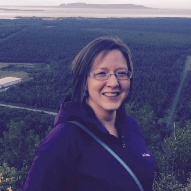 A smiling Tricia McGuire-Adams stands before a forested valley that bordered by water in the distance.