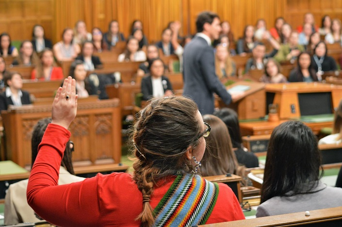 A young woman in the House of Commons raises her hand to ask a question of Prime Minister Trudeau, standing at a podium.