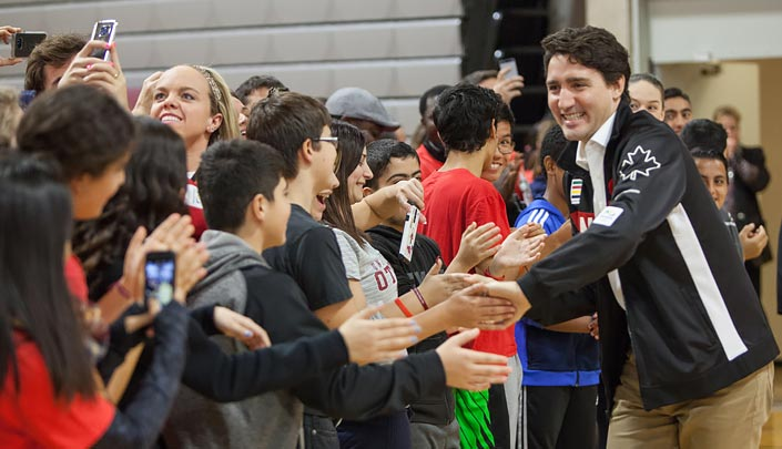 Prime Minister Justin Trudeau, wearing a jacket with a maple leaf, greets a group of people with handshakes.