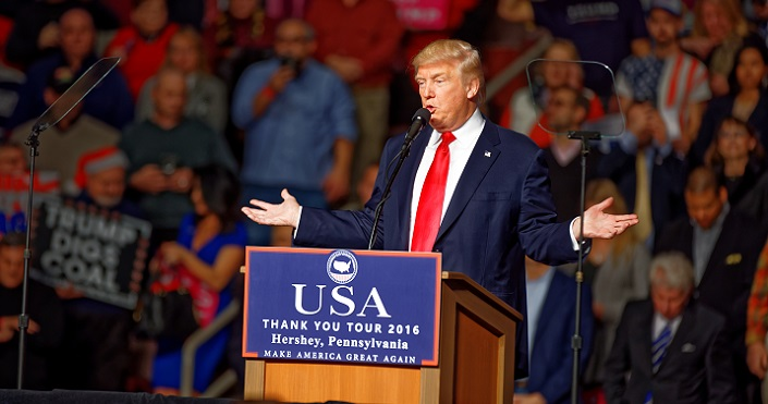 Donald Trump sur le podium, les partisans en arrière-plan.