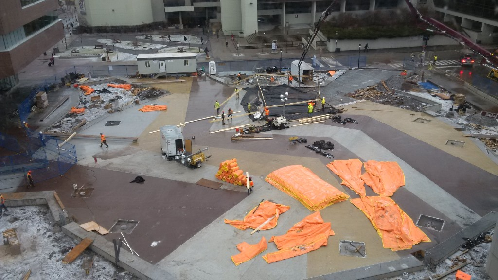 University Square construction site with coloured concrete paths in a zig-zag pattern. Tarps cover the ground and construction workers are busy.