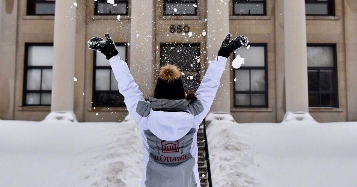 Un individu portant un manteau avec le logo de l'Université d'Ottawa jette de la neige en l'air, celui-ci a été photographié par derrière.