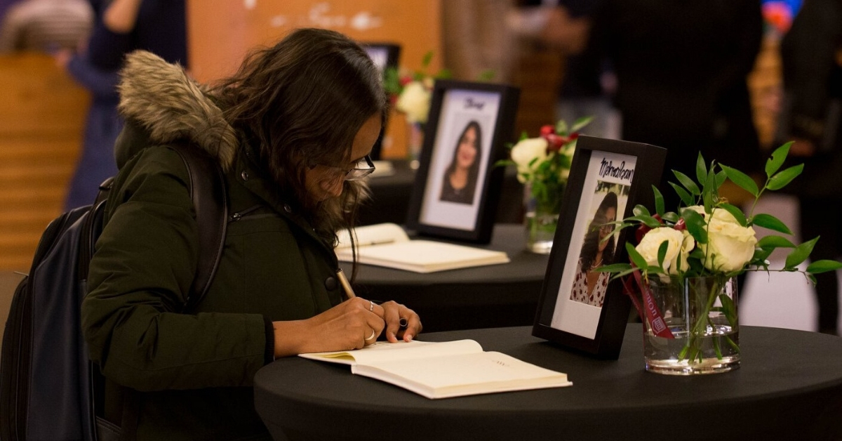 A woman signs a book of condolences.