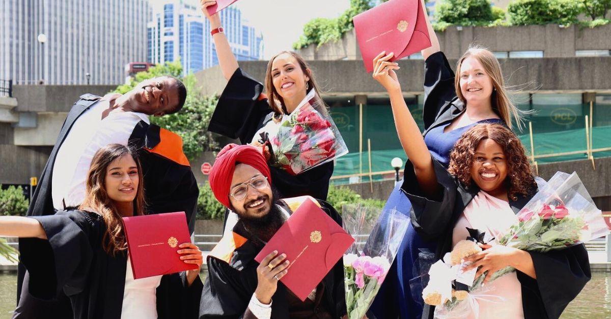 Un groupe de nouveaux diplômés près du canal Rideau, ils tiennent des diplômes et des bouquets.