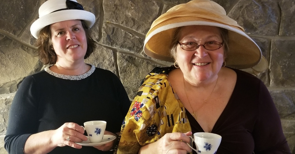 Two women holding tea cups, they are wearing hats.
