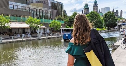 An alumna is facing away with a convocation robe draped over her shoulder. The Parliament of Canada and Rideau Canal appear the background.