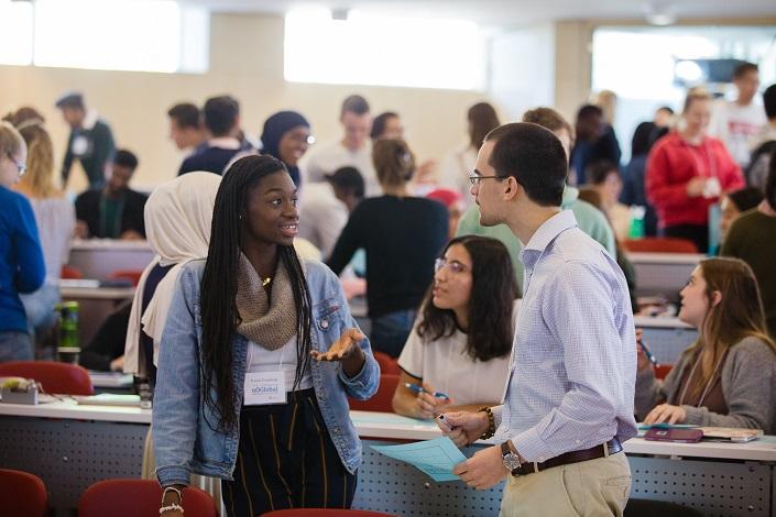 Deux étudiants discutent en classe; derrière eux, un groupe diversifié d'étudiants est aussi en discussion.
