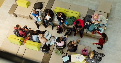 About a dozen students, seen from above, sitting together and chatting.