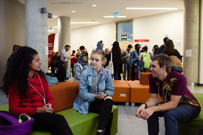Deux étudiantes et un étudiant discutent ensemble pendant la pause.