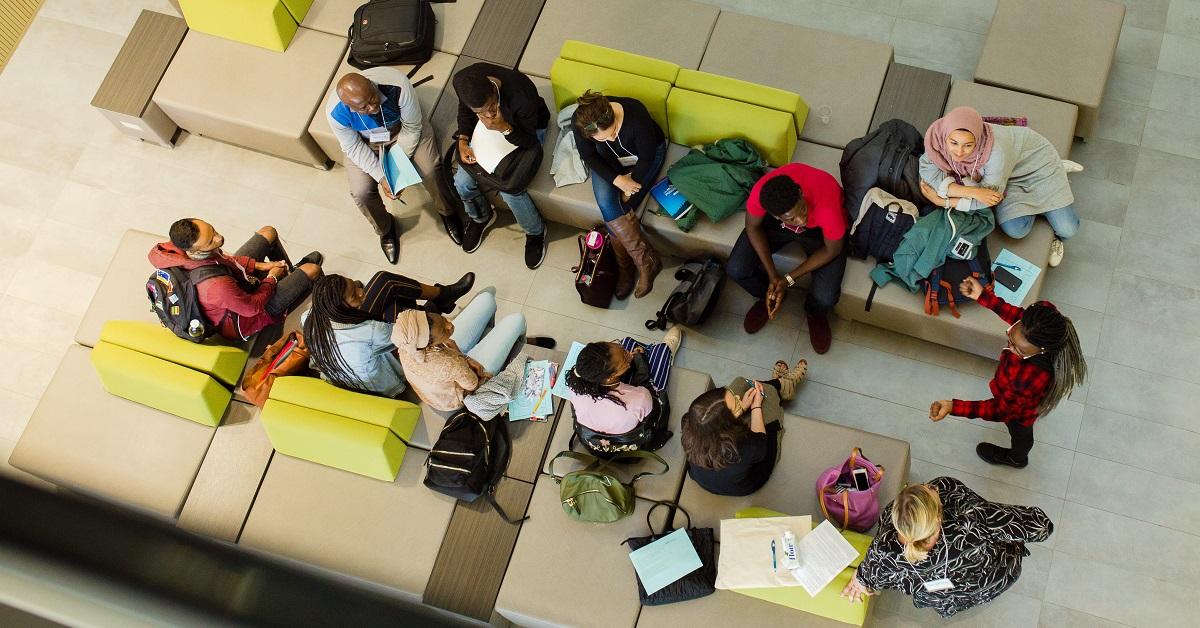 Vue d'oiseau d'une douzaine d'étudiants discutant en groupe.