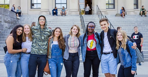 A diverse group of uOttawa students linking arms outside Tabaret Hall.