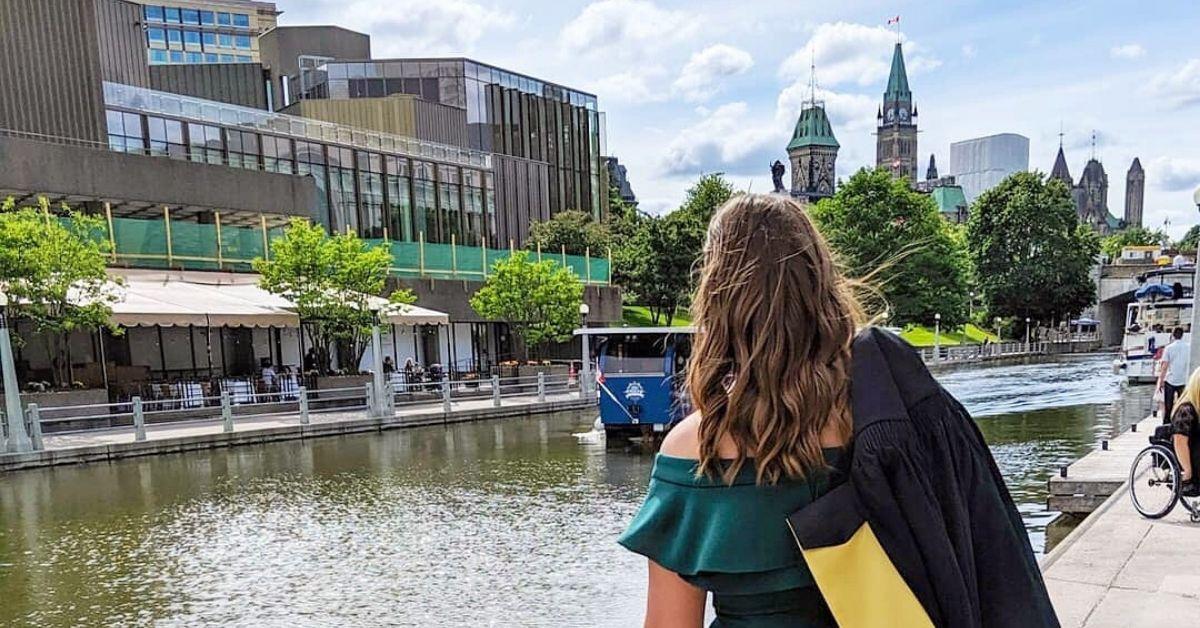Une diplômée fait dos à la camera. Elle a une toge de la collation des grades sur l'épaule. Le Parlement du Canada et le canal Rideau apparaissent en arrière-plan.