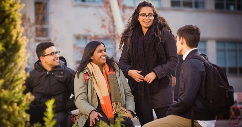 Quatre étudiants bavardant sur le campus de l'Université d'Ottawa.
