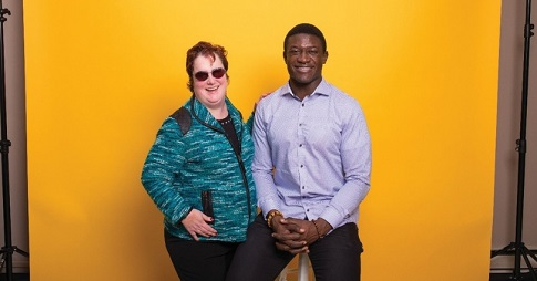 A female donor and a male student pose in front of a yellow backdrop.