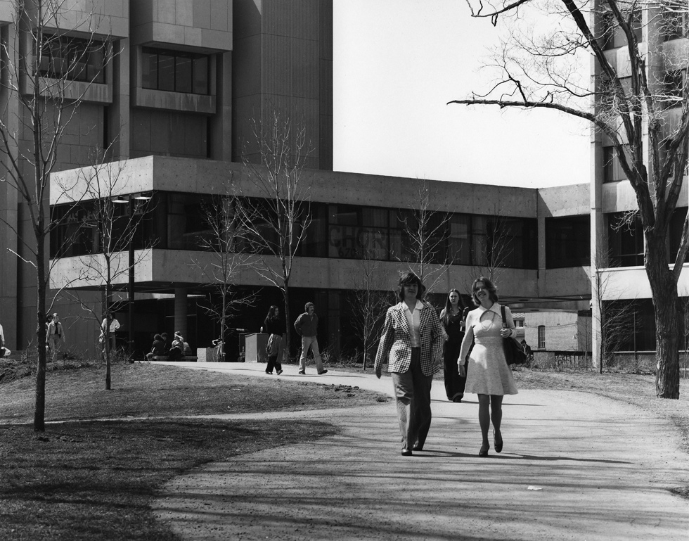 Black and white photo of two female students walking on campus in 1970.
