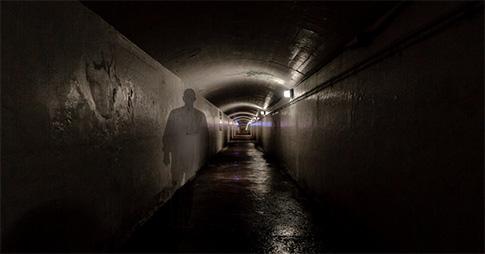 Un tunnel avec l'ombre d'un homme projeté sur le mur.
