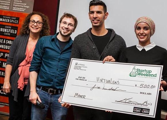 Quatre personnes souriantes se tiennent en rangée. Deux d'entre elles tiennent un chèque en format géant au montant de 500 $.