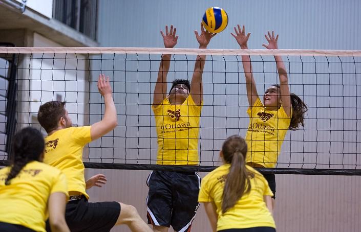 Cinq étudiants jouent au volleyball.