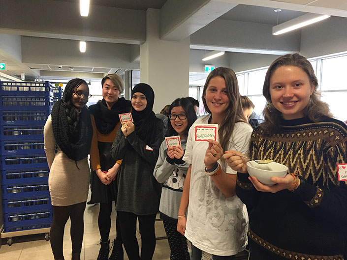 Six smiling women are showing cards with 'Ask me why I'm awesome' on them. One of them holds a bowl and a spoon.