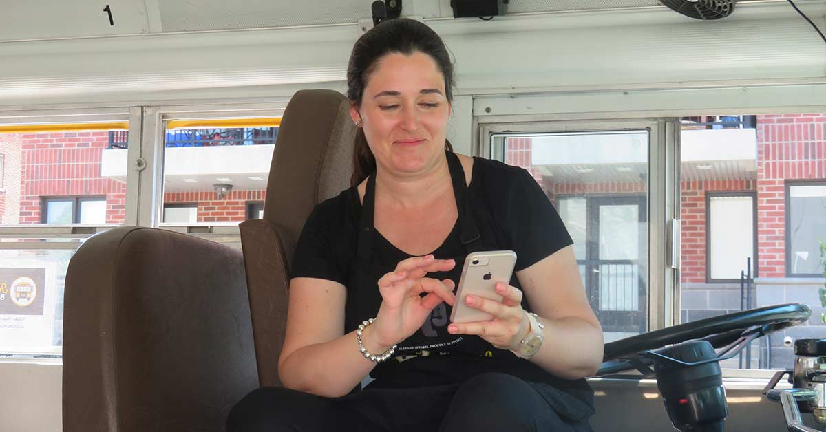 Anne donovan looking at her cell phone while sitting in the driver's seat.