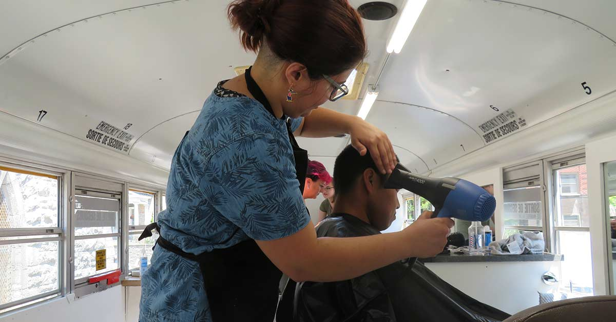 A volunteer hairdresser dries hair of a user.