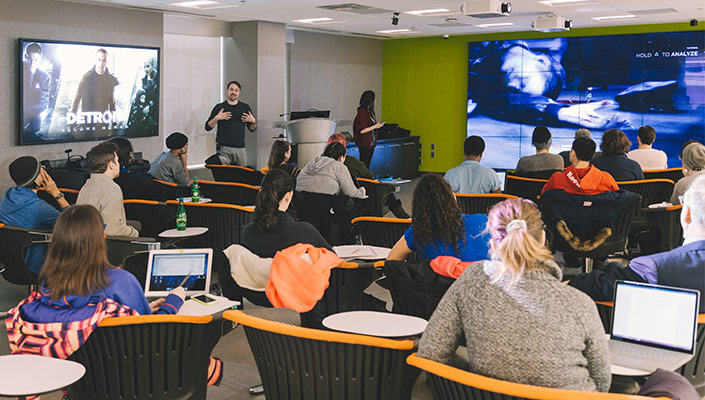 Students watch video games play on giant screens on a classroom wall, as the professor and a student playing the game stand at the front of the class.