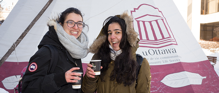 Two students smiling in front of a uOttawa branded tent holding cups of coffee.