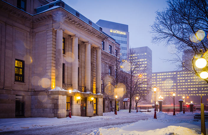 The northern side of Tabaret Hall in winter with the Desmarais Building in the background.