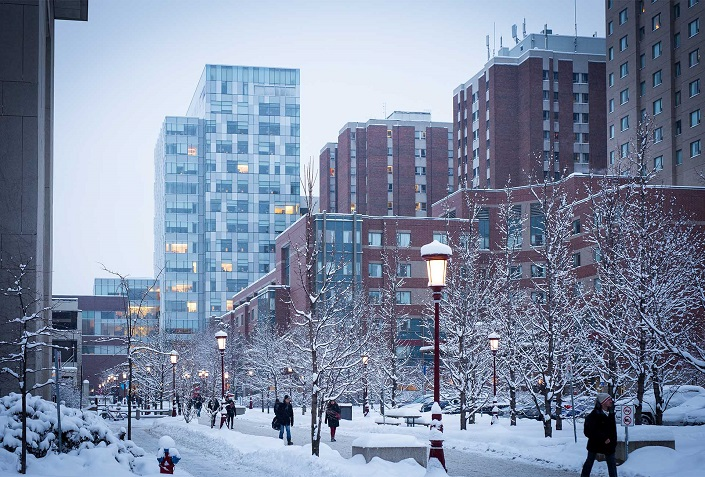 Winter scene showing students walking by high-rise buildings on campus