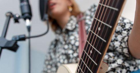Une femme joue de la guitare tout en chantant dans un micro.