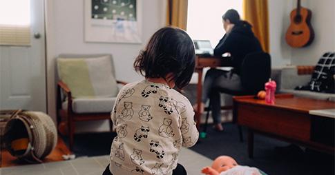 Un petit enfant joue avec une poupée pendant que sa mère travaille en arrière-plan