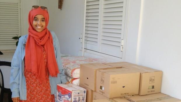 Zein Ahmed sourit devant des boîtes et des paquets.