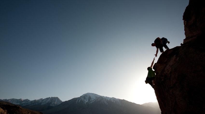 A climber helping another climber climb a mountain