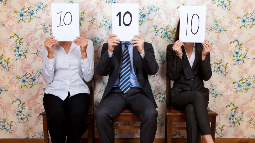 A man and two women dressed in business attire hold sheets of paper in front of their faces indicating perfect 10 scores.