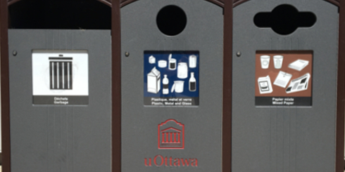 close-up of recycling and garbage bins outside a building