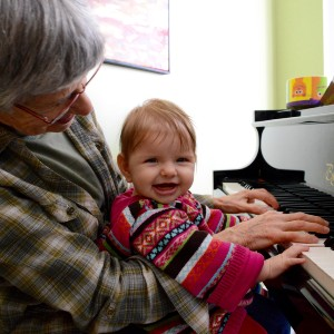Elderly woman with baby at piano