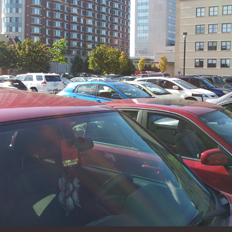 Lot K full of parked cars. A parking permit is visible in one of the windshields