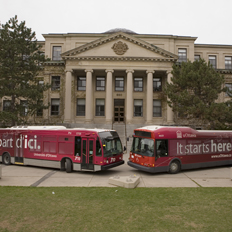 STO and OC Transpo buses are parked in front of Tabaret Hall, showing the uOttawa colors