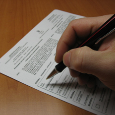 A person's hand signing the permit application form