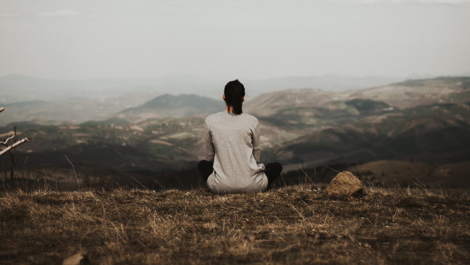 Une femme médite dans la nature, regardant l'horizon.