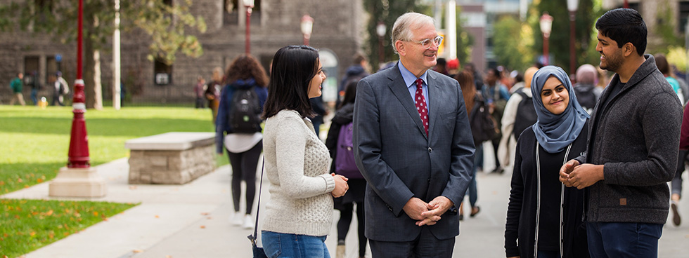 uOttawa President, Jacques Fremont, in conversation with students in front of Tabaret Hall.
