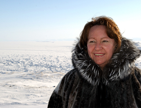 Sheila Watt-Cloutier wearing a fur-lined parka stands smiling in a snow-covered Arctic landscape.