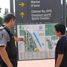 Protection Services' guard showing instructions on campus map to a student