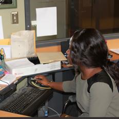 Jeune étudiante bénévole assise au bureau de la protection communautaire, regardant l'écran d'ordinateur
