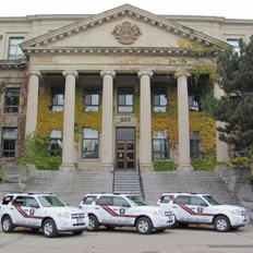 Three Protection Services' white service cars parked in front of Tabaret Hall