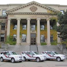 trois véhicules blancs du Service de la protection stationnés devant le pavillon Tabaret