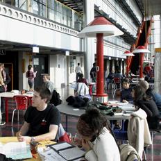 Des étudiants sont assis à des tables du pavillon ÉITI