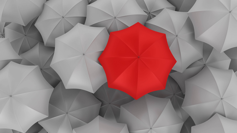 Un parapluie rouge parmi des parapluies gris