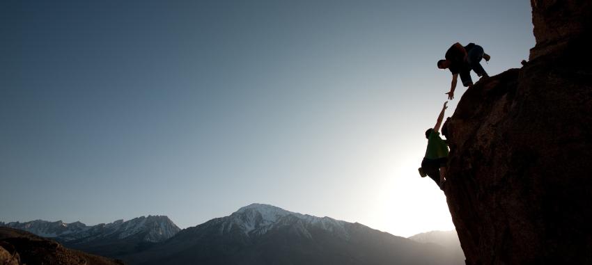 Un grimpeur aide un autre grimpeur a escaladé une montagne