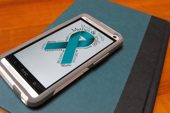 """Cellphone on a book whose screen shows the image of a teal ribbon with the words """"Myths & reality"""""""